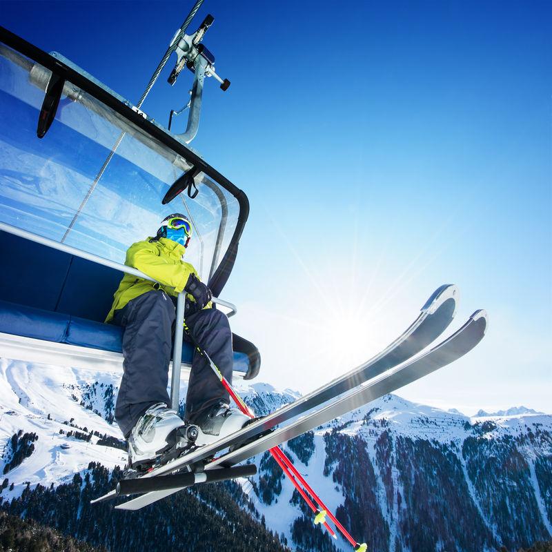 坐在高山滑雪缆车上的滑雪者