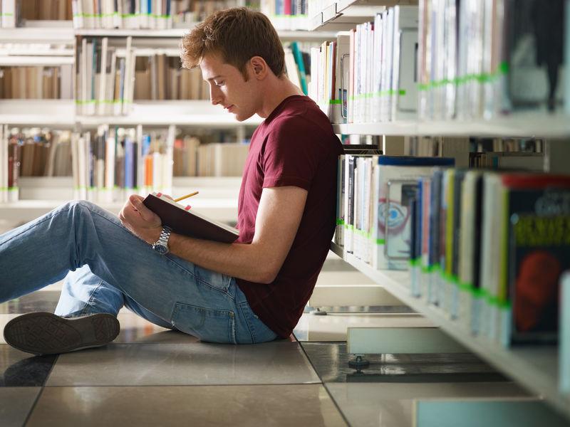 男大学生坐在图书馆的地板上看书-水平形状-侧视图-四分之三长度-复制空间
