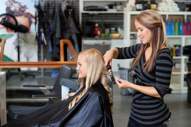 年轻造型师卷发女士的侧视图在美发沙龙呈现出新的发型
