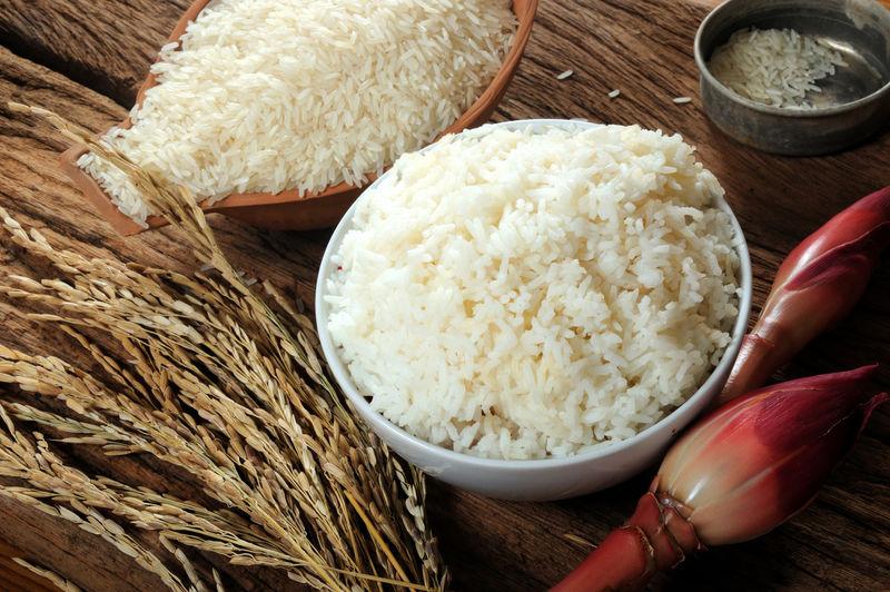 木桌上的炒饭、生米和稻米;三种水稻