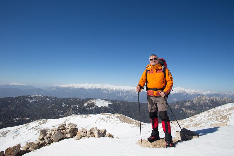 冬天在雪山上徒步旅行,背着背包和帐篷。