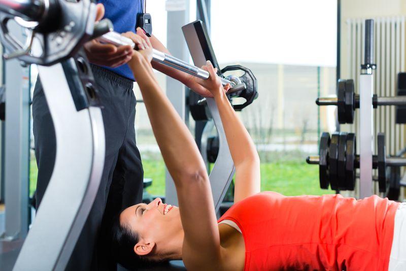在健身房里-一个带着私人健身教练的女人用哑铃锻炼身体-她在举重台上用杠铃