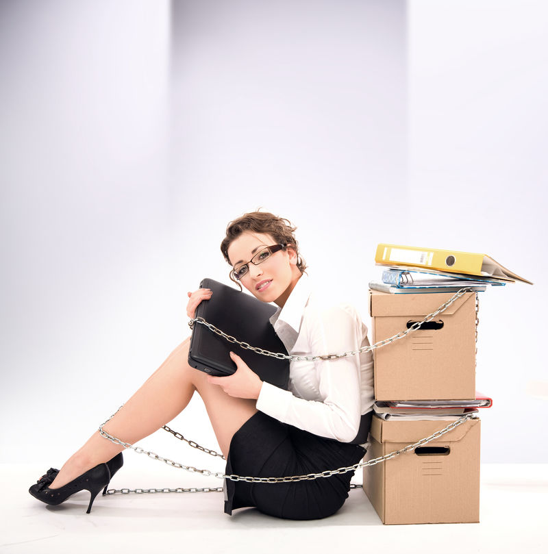 坐在成堆文件旁边的成功的年轻女商人
