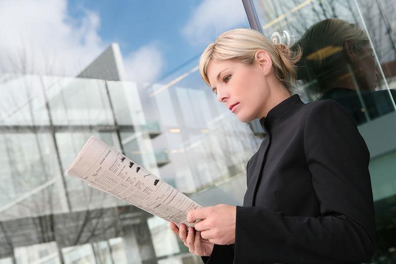 一位美丽的金发女商人在看报纸