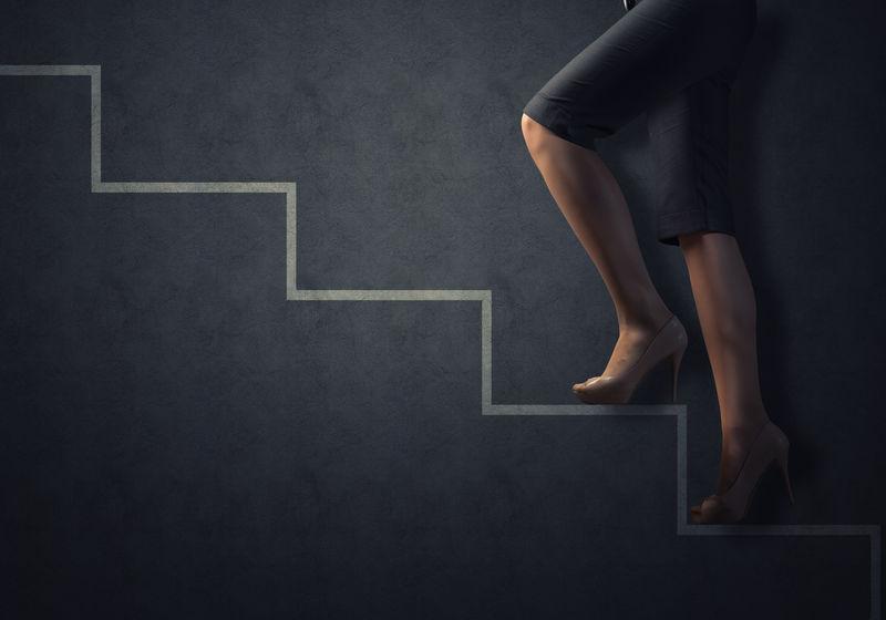 商业女性的双腿被拉上了楼梯-成功的商业理念