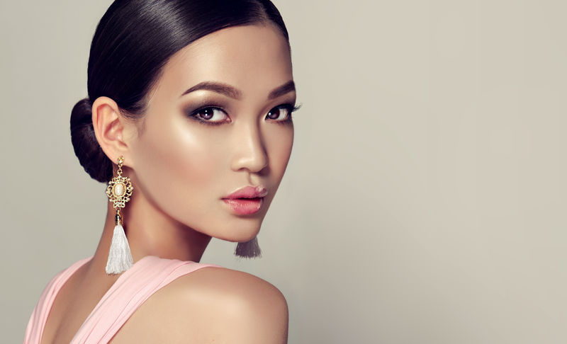 亚洲时装模特-戴着流苏耳环和粉色连衣裙