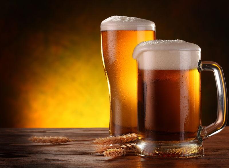 两个浅啤酒杯-深黄色背景上有大麦小穗