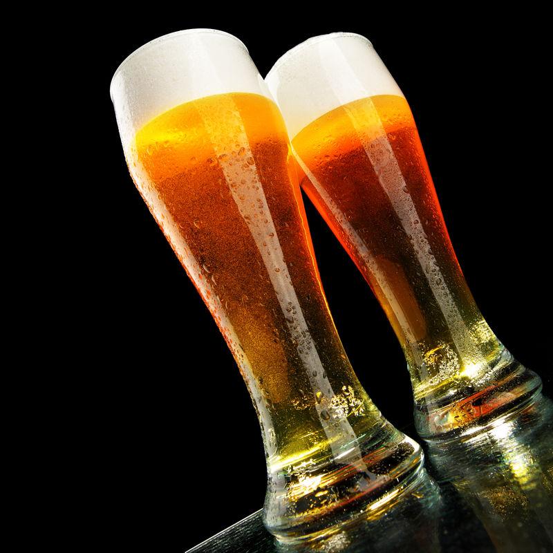 两杯黑底泡沫啤酒