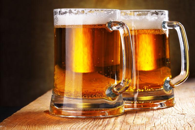 木桌上的两个啤酒杯特写镜头