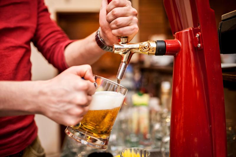 酒吧招待在酒吧或酒吧里酿造未经过滤的生啤酒