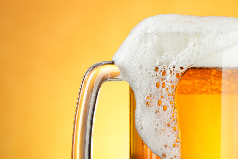 黄色背景上有泡沫的啤酒杯