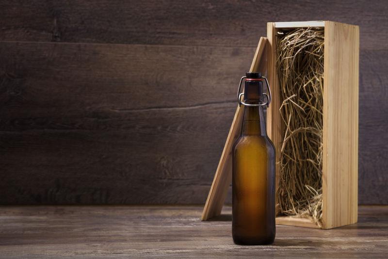 手工制作啤酒瓶模型-没有标签的啤酒瓶-木制礼品盒放在乡村桌子上