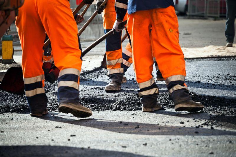 道路施工、工业和团队合作的工人-在柏油路上用铲子工作的人