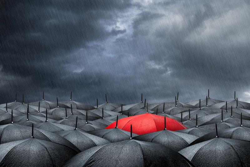 手上拿着一把红色的雨伞-一大堆黑色的雨伞