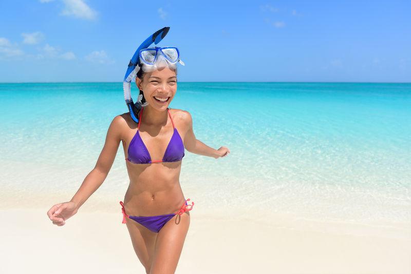 海滩度假-亚洲女子游泳乐趣。美丽性感的年轻女性成年人,带着潜水面罩,穿着紫色比基尼,在她的旅游假期里从水里跑出来。