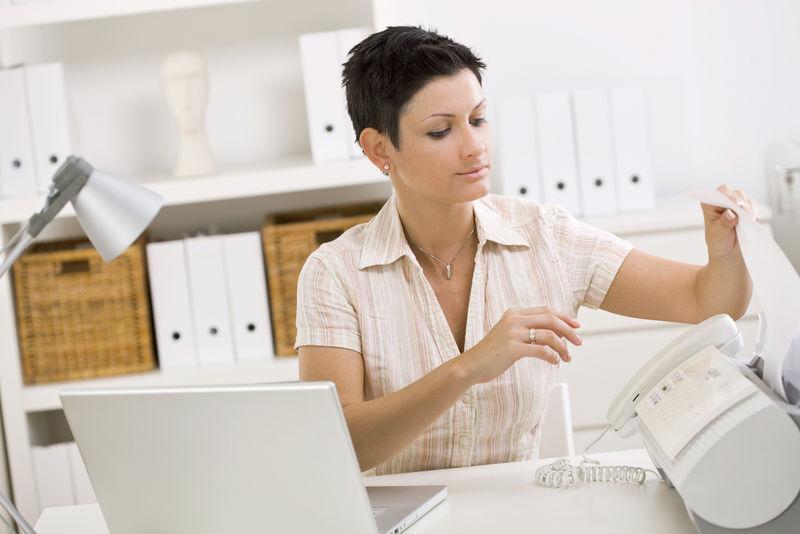 在家庭办公室使用传真机的妇女。