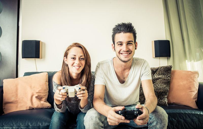 年轻夫妇在客厅玩电子游戏-家庭娱乐概念