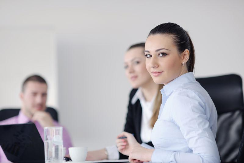 成功的商业女性与她的员工站在现代明亮办公室的背景下