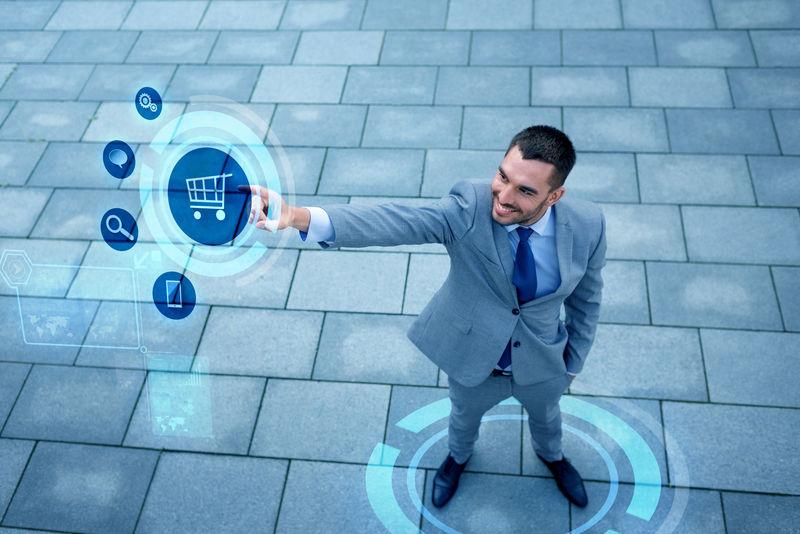 商业、销售、技术和人的概念-年轻的微笑的商人从顶部指向虚拟屏幕上的购物车图标