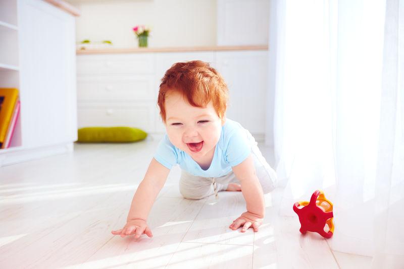 可爱的姜黄色小男孩在家里爬在地板上