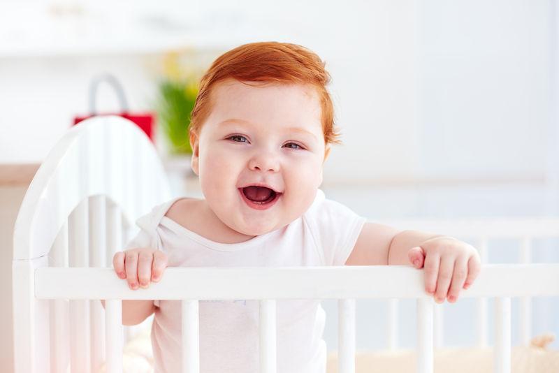 可爱的快乐婴儿站在家里的婴儿床上