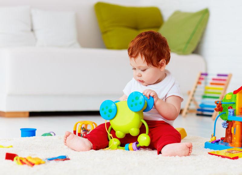 可爱的红头发婴儿在家玩玩具