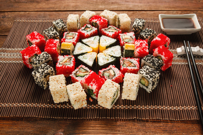 美食艺术,烹饪杰作。一套很棒的寿司,点缀在棕色草席上,特写镜头。豪华餐厅菜单照片。