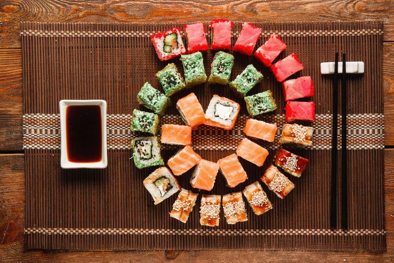 日本寿司,美食艺术。一大套新鲜的面包卷在棕色的草席上呈彩色螺旋状,平放。豪华餐厅菜单照片,传统东方美食。