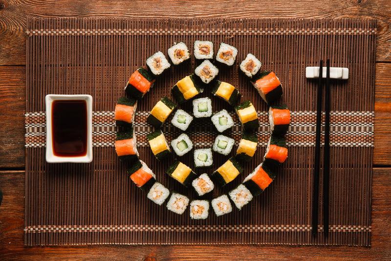 日本美食艺术。美味的Uramaki卷轴套装,彩色圆形寿司点缀在棕色草席上,平放。豪华餐厅菜单照片。