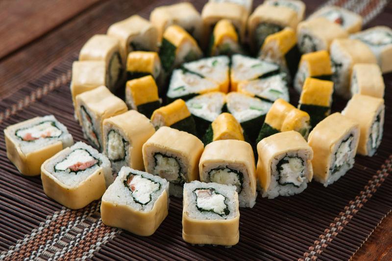 美味的五颜六色美味的寿司卷,放在草席上,特写。日本豪华餐厅菜单照片,传统海鲜。