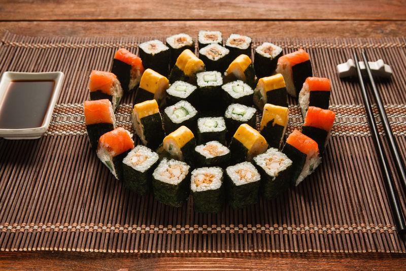 色彩鲜艳的日本寿司套装,棕色草席上的卷形装饰,特写。日本美食艺术,民族美食,餐厅菜单照片。