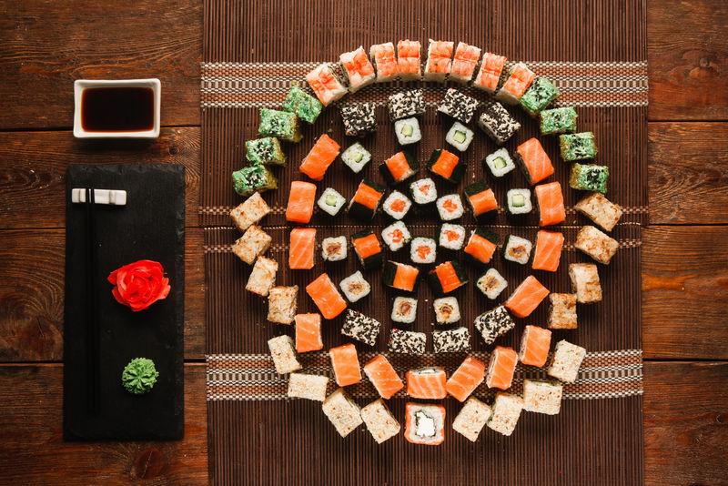 美食艺术,美味的寿司套装。各种各样的开胃面包卷,棕色草席上的彩色圆形装饰,平铺。豪华日本餐厅菜单照片。