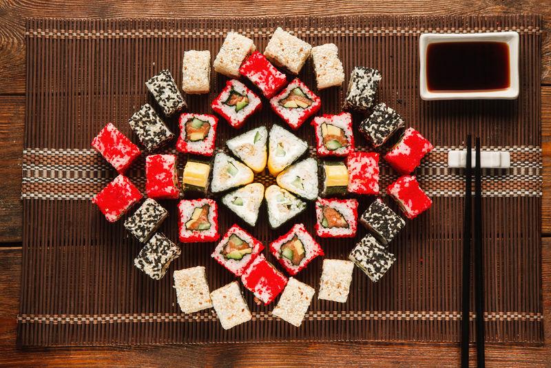 一套五颜六色的美味寿司,铺在棕色的草席上,平摊着。美食艺术,美丽的装饰。日本料理,餐厅菜单照片。