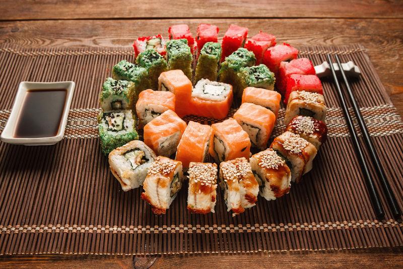 丰富多彩的日本寿司,美食艺术。美味的乌拉马基卷呈彩色螺旋形摆在棕色草席上,特写。东方豪华餐厅菜单照片。