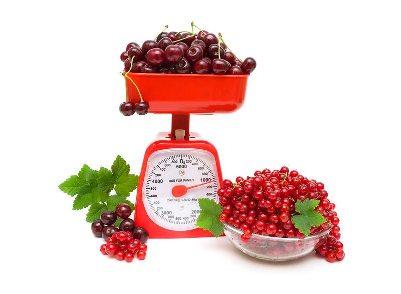 红醋栗和樱桃,白色背景的厨房鳞片。