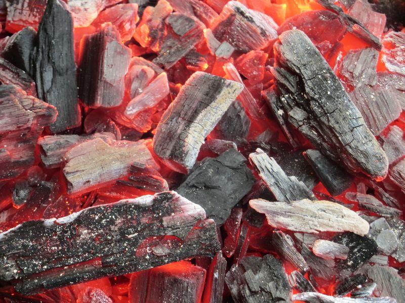 在黑暗中燃烧的炭的特写镜头-烤肉架上的灰烬