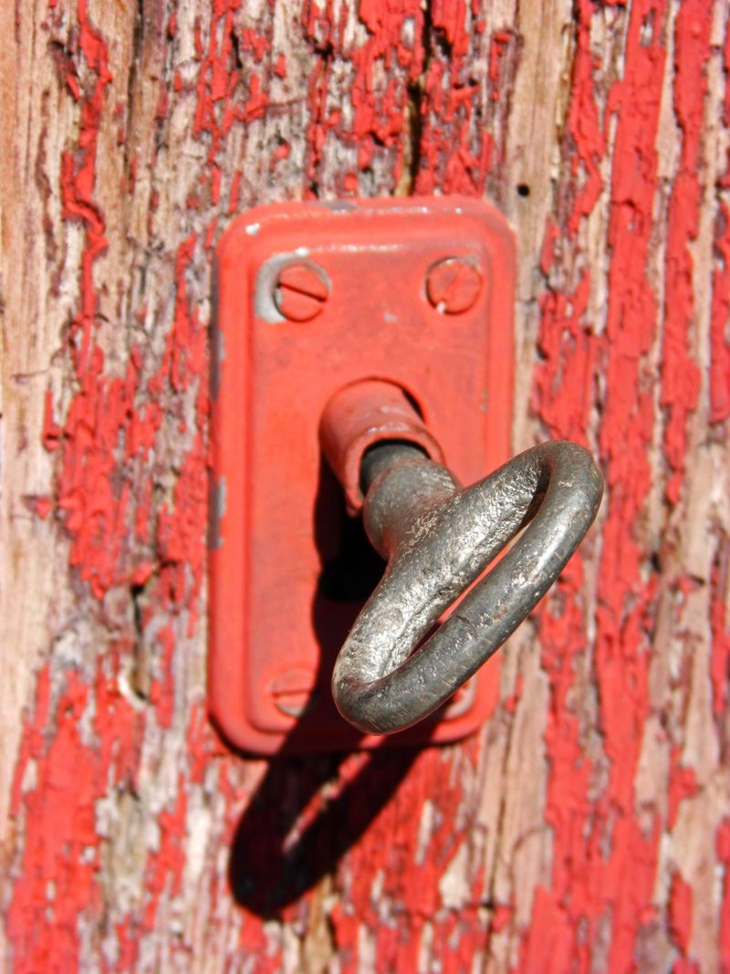 古老的铁制钥匙从门上挂在古老的红色木门上