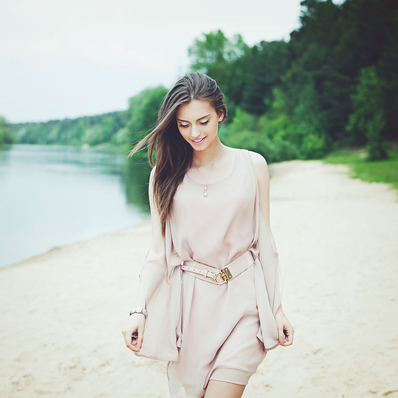 穿着白衣服的漂亮女孩走在湖边