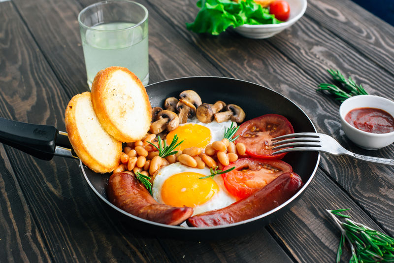 早餐番茄、香肠、豆类、蘑菇、鸡蛋、吐司和香草
