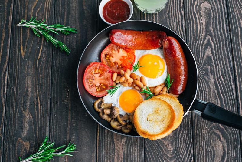 早餐番茄、香肠、豆类、蘑菇、鸡蛋、吐司和香草俯视图
