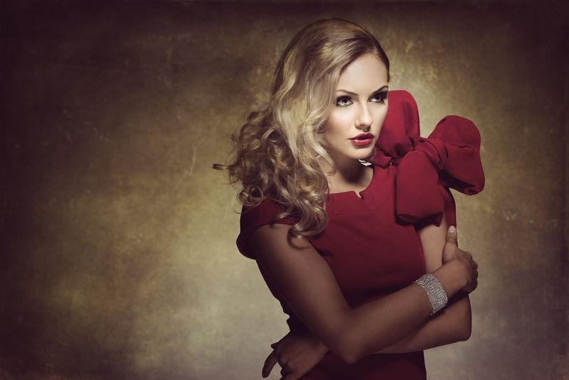 金发女郎-穿着红色连衣裙-发型新颖-一面看着-她有一个大蝴蝶结