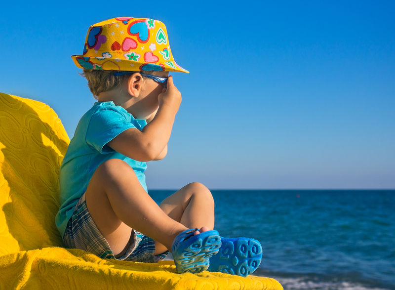 小孩坐在黄色的躺椅休息室里-看着大海