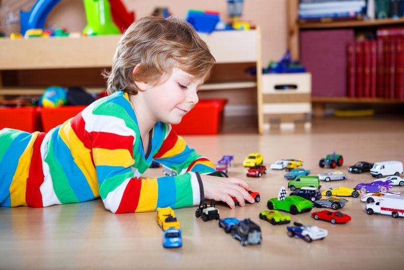 快乐有趣的小金发小孩在室内玩很多玩具车-男孩穿着彩色衬衫-在托儿所玩得很开心