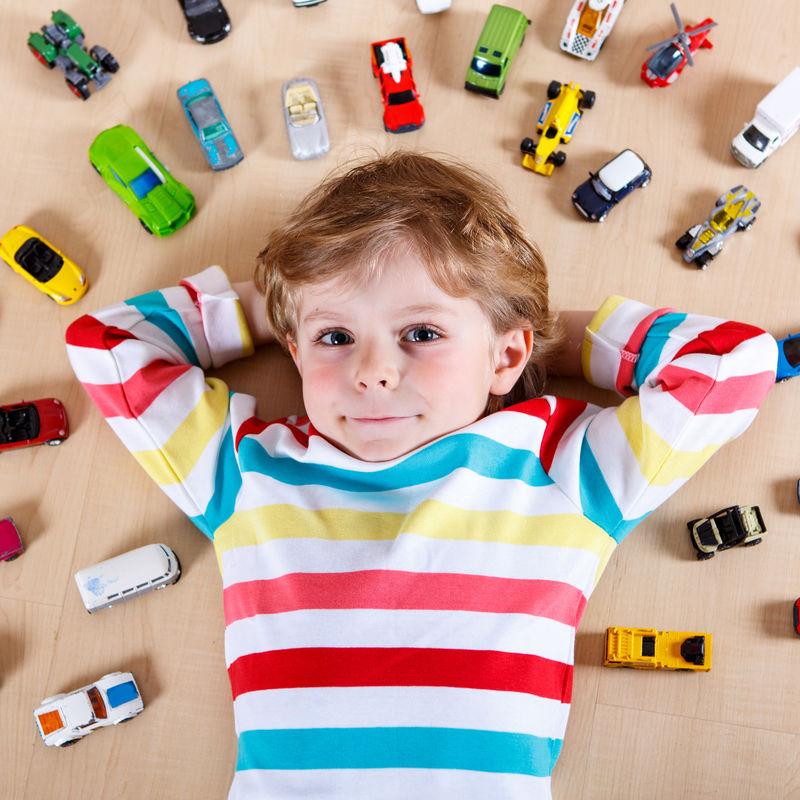 小金发小孩在室内玩很多玩具车-男孩穿着彩色衬衫-玩得很开心