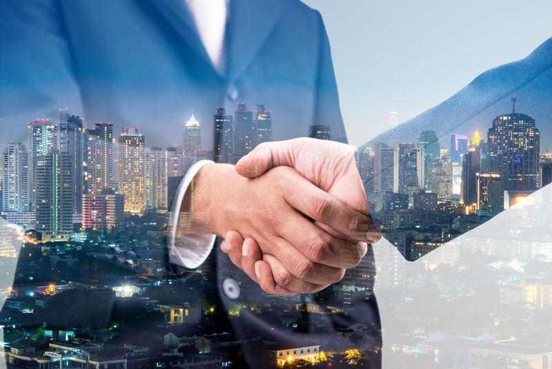 商业交易与城市夜背景、团队合作和合作理念的双重握手