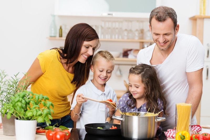 快乐的年轻家庭-妈妈-爸爸和两个孩子一起在厨房做饭-一起准备意大利面