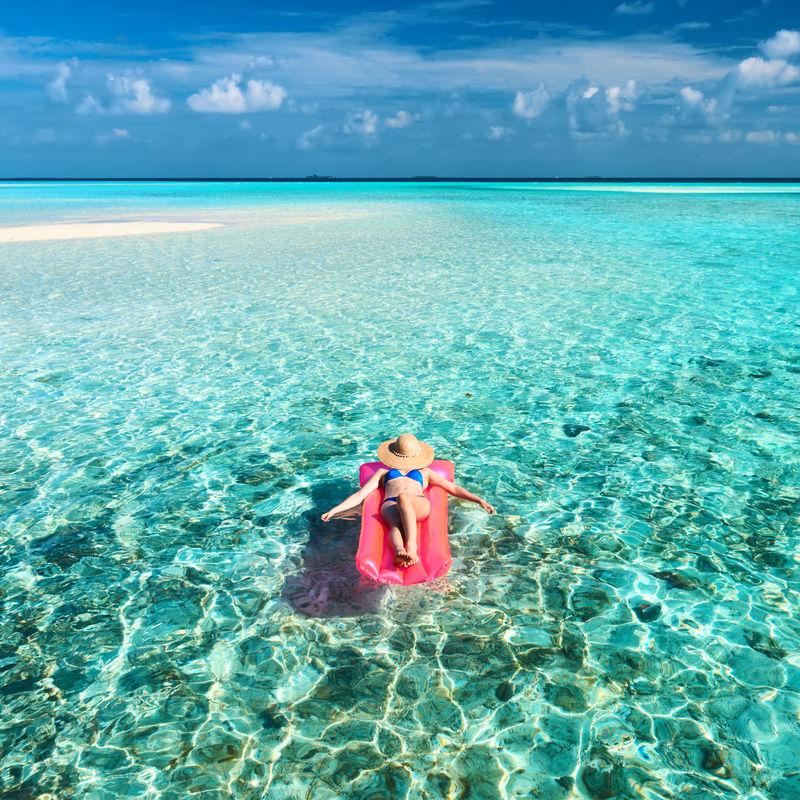 在海滩上用充气床垫放松的女人