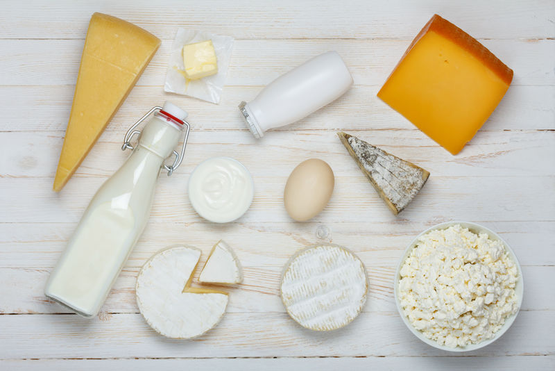 木制桌子上的乳制品分类-牛奶、奶酪、鸡蛋、酸奶、酸奶油、农家干酪和黄油