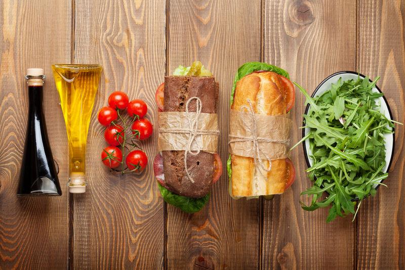 两个三明治-配沙拉、火腿、奶酪和西红柿-沙拉和香料放在木桌上-带复制空间的俯视图