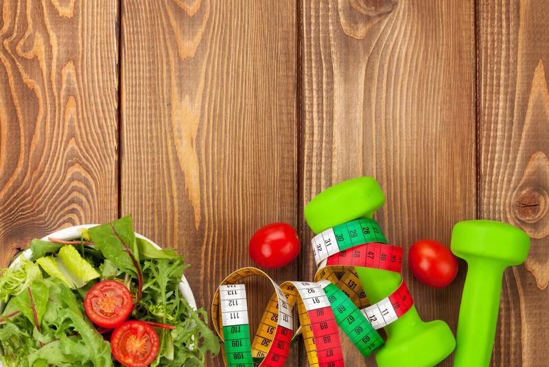 哑铃、卷尺和健康食品放在木制桌子上-有复印空间-健康与健康